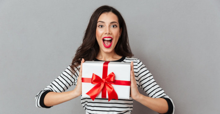 Portrait of a happy girl holding present box and looking at camera with mouth open isolated over gray background